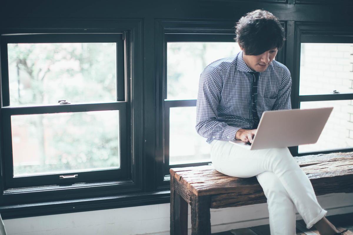 ベンチでパソコンをする男性